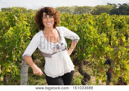 a Winegrower woman standing in vine rows