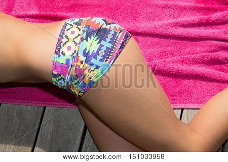 Beautiful young girl in colored bikin on the deck of a pool