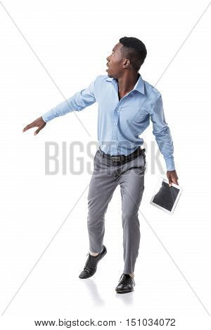scared African-American businessman runs and looks around. isolated on white background. pressure on business