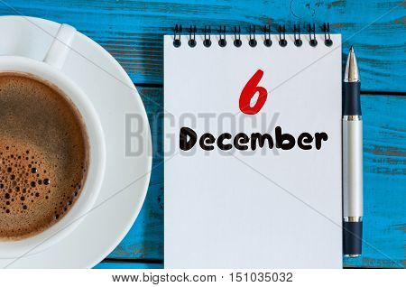December 6th. Day 6 of month, calendar on freelancer workplace background with coffee cup. Top view. Winter time. Empty space for text.