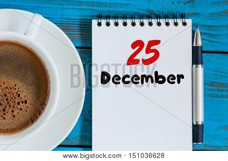 December 25th Eve Christmas. Day 25 of month, calendar on workplace background with morning coffee cup. New year concept. Empty space for text.
