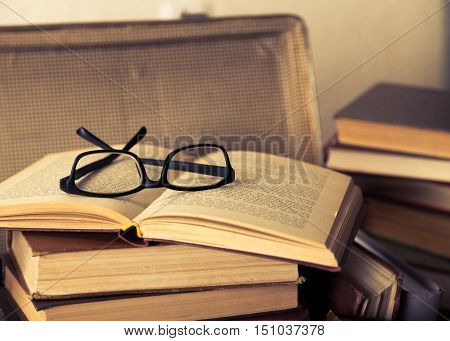 Close up of a pile of books and a pair of eyeglasses in an old suitcase, with a retro effect