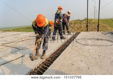Tyumen, Russia - July 31, 2013: JSC Mostostroy-11. Workers teamwork on road construction. Bridge construction for outcome of the Tobolsk path and Bypass road round Tyumen.