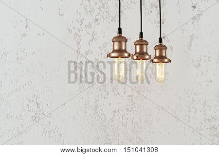 Industrial pendant lamps against rough wall. Loft interior. Edison bulbs.