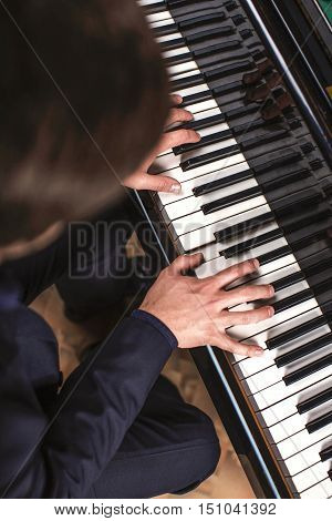 Talent and virtuosity. Top view of handsome young men playing piano