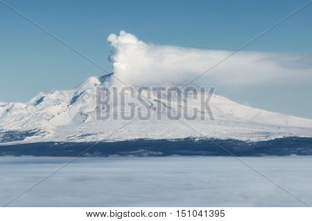 Volcanic landscape of Kamchatka Peninsula: erupting active Shiveluch Volcano in explosion of magmatic gases accompanied by release of crater of volcano of large masses of steam ash. Eurasia Russia Far East Kamchatka Region.