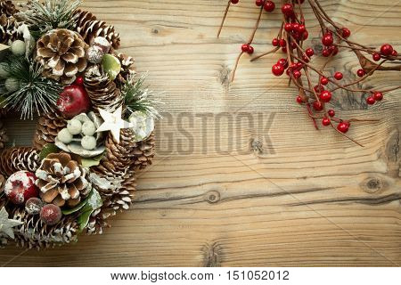 Christmas wreath formed by natural elements and branch with red fruits