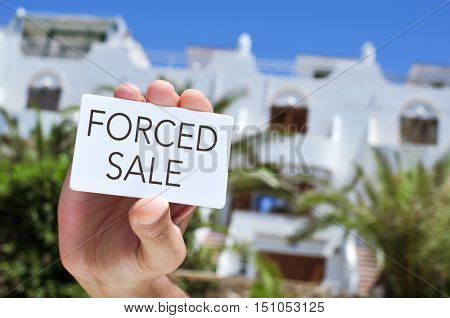 closeup of the hand of a young man showing a signboard with the text forced sale, in front of a house