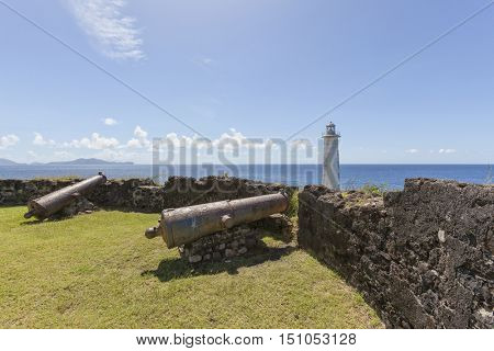 Old cannons and lighthouse at Vieux-Fort, Basse-Terre, Guadeloupe