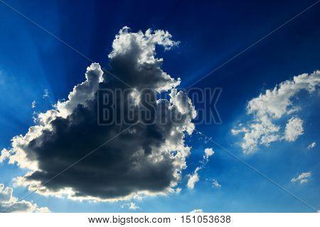 Blue sky with sunbeams shining through the dark cloud.