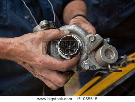 the hands of mechanics hold the turbine of a car motor