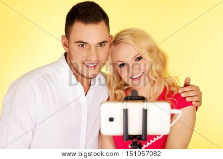 Happy couple taking selfie photo with selfie stick