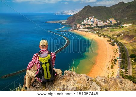 tourist man sitting on the edge of a cliff looking at the beach Playa de Las Teresitas Canary Islands Spain