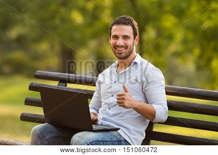 Successful businessman is showing thump up while using laptop and sitting at the park.