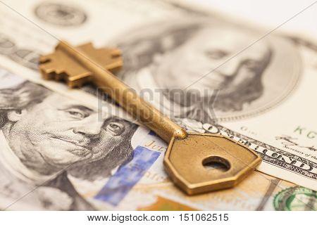 Closeup of key on hundred dollar US bills