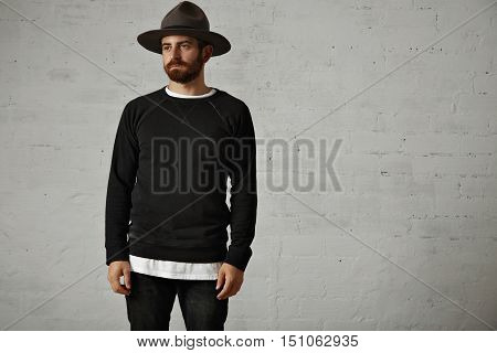 Sad looking young bearded man in blank black longsleeve cotton sweatshirt and felt mountain hat in a studio with white brick walls