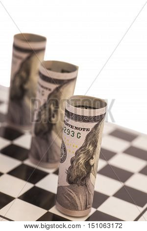 Hundred dollar bills on chess board isolated on white background