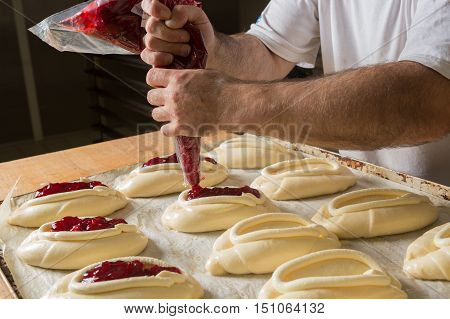 Raw sweet yeast dough on a baking sheet filling buns jam. Preparation for baking. The concept of chefs and baking.