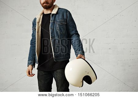 Unrecognizable brutal young motor biker wears shearling denim jacket and black blank henley shirt, holds vintage beige motorcycle helmet, isolated in center of white brick wall