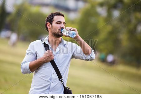 Young businessman is drinking water and resting from work at the park.