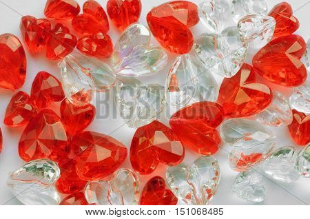 colored plastic heart on white paper background