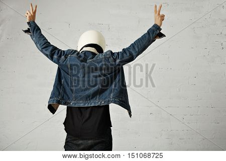 Back view on fit body of brutal younf motocyclist wears helmet, black longsleeve henley shirt and club denim jacket with his hands up showing peace gesture