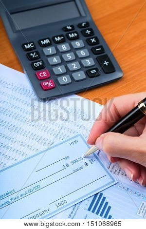 Close-up of a Businesswoman Signing a Check on Desk