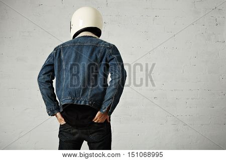 Back view on fit body of brutal younf motocyclist wears helmet, black longsleeve henley shirt and club denim jacket with his hands in back pockets of his trousers