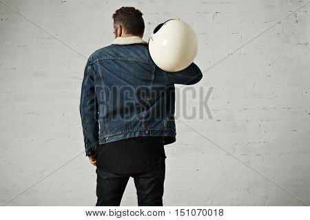 Spine view of biker wears shearling denim jacket and black blank henley shirt, holds vintage beige motorcycle helmet, isolated in center of white brick wall poster
