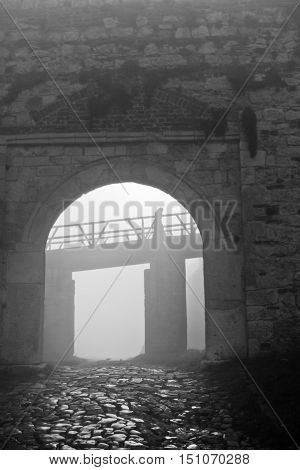 Fortress gate and wooden bridge in fog at autumn morning, Kalemegdan, Belgrade, Serbia