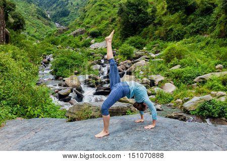 Yoga outdooors - woman doing yoga asana eka pada urdva dhanurasana Upward Bow Pose back benkd outdoors at waterfall in Himalayas