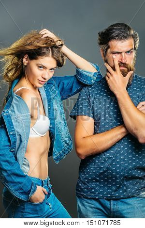 Fashion couple of pretty girl in bra denim jacket and handsome bearded man hipster pose on grey background