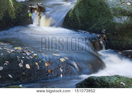 Close up on the rushing waters of Burbage Brook, a stream flowing through the rocky valley of Padley Gorge, Peak District, UK