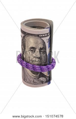 Hundred dollar bills rolled up with rubber band on white