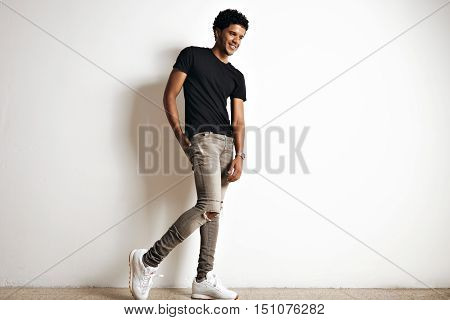 Full body shot of a cute tall young African American model with an afro in a plain black cotton t-shirt, white sneakers and slim grey jeans isolated on white