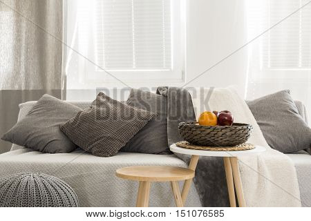 Light interior with window sofa pouf decorative pillows and side tables
