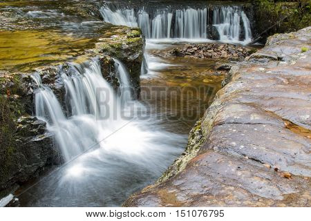 Sgwd Y Bedol waterfall on the Nedd Fechan along the Elidir trail in South Wales UK.Long exposure with motion blur