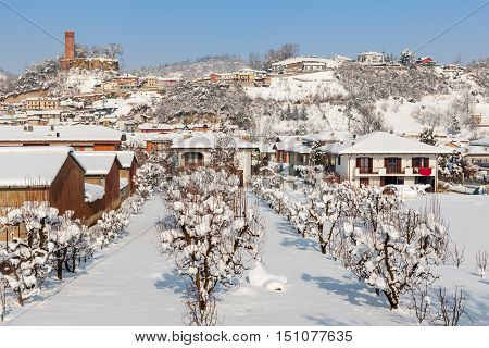 Small town covered with snowy under blue sky in Piedmont, Northern Italy.