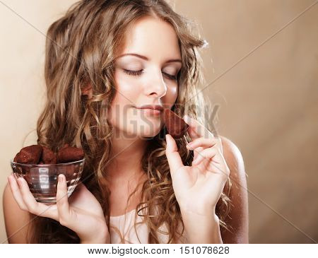 Beautiful curly woman eating a chocolate bonbon