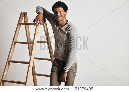 Smiling relaxed tall muscular young model wearing a plain heather gray longsleeve t-shirt and slim gray jeans leaning on a wooden stepladder isolated on white.