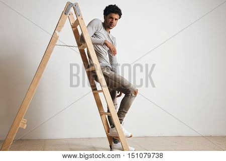 Young sexy latin guy wears blank grey henley longsleeve and jeans sits on wooden ladder , isolated on white and looking on camera