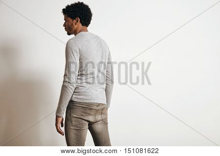 Back view of attractive latino man looking on side, isolated on white, wearing blank heather grey clothing