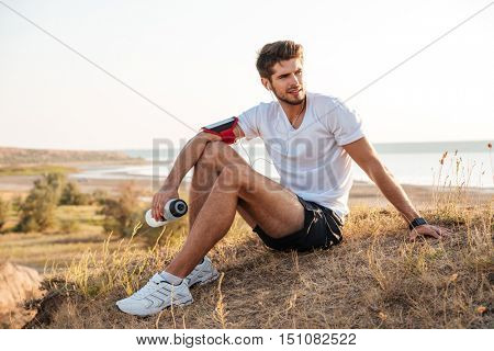 Full length portrait of handsome young sportsman sitting and holding bottle of water outdoors