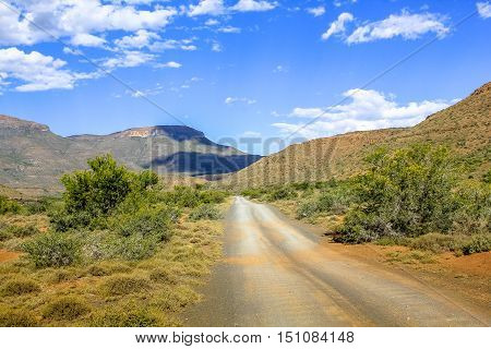 Adventure in African desert. Gravel mountain road in Karoo National Park, Western Cape, South Africa. Dry season. The parks of South Africa are famous for the magnificent scenery and wildlife.