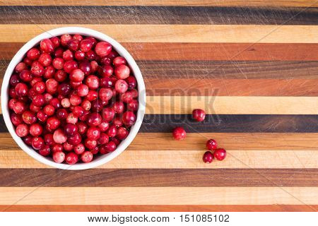 Bowl Of Fresh Ripe Cranberries On A Cutting Board