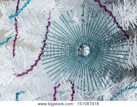 close up horizontal image of a beautiful blue sparkly christmas ornament with blue diamond in the middle hanging on a white christmas tree with blue and red streamers.