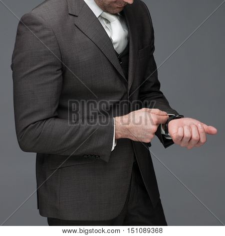 Business man adjusting his sleeve on a grey background stock picture