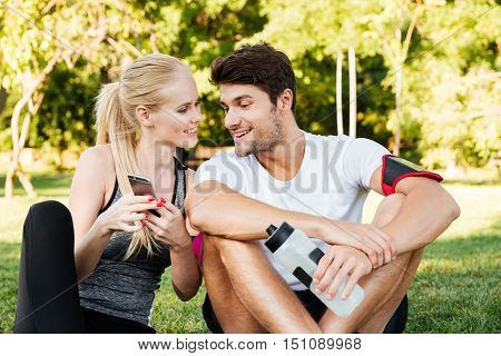 Smiling young woman and personal trainer with smartphone resting after jogging outdoors