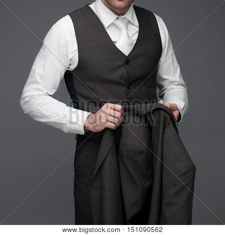 Business man standing with jacket in his hands on a grey background stock picture