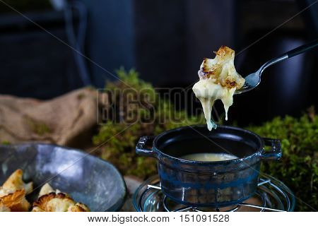 Roasted cauliflower with white sauce, which is poured into a small pan. You can use for a Healthy lifestyle, for vegetarian cuisine, for a romantic evening.